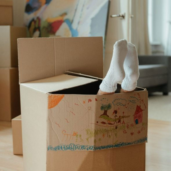 Kid Playing in Moving Boxes   We Organize Florida - Professional Home, Office, and Retail Organizers in Southwest Florida